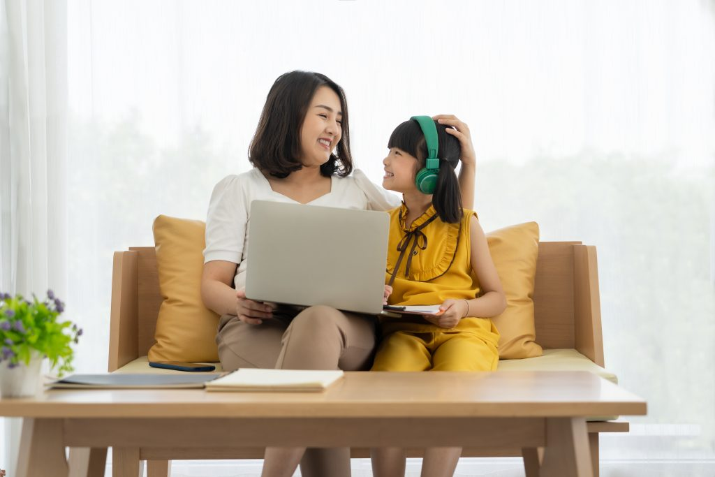 asian mother with laptop teaching child during online class