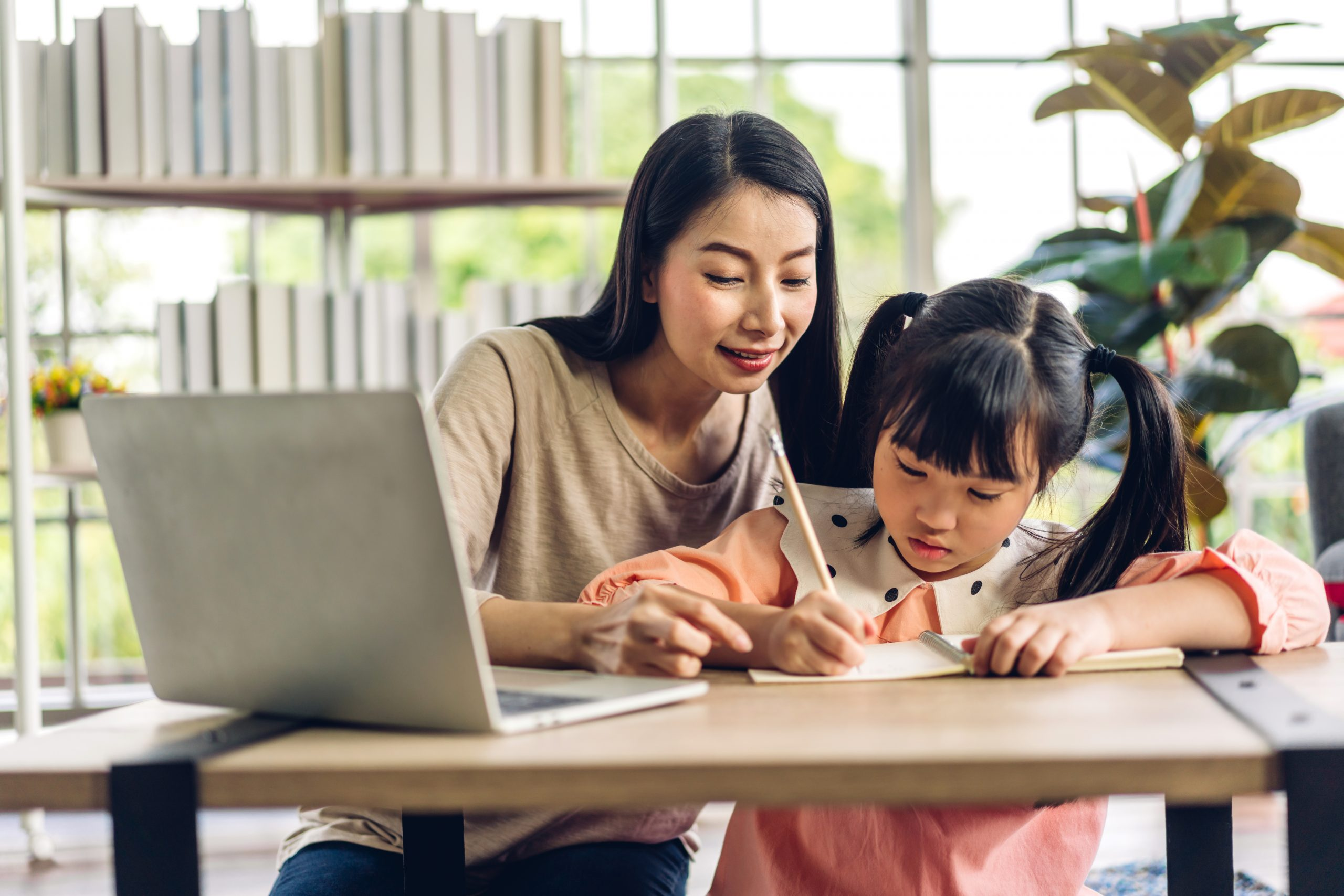 asian mother teaching little kid with assignment